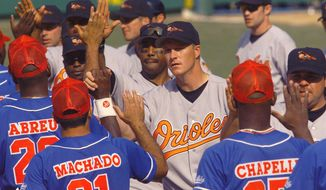 FILE - In this March 28, 1999 file photo, Baltimore Orioles pitcher Mike Timlin, center, and teammates are congratulated by the Cuban national team following the Orioles' 3-2 win in extra innings in Havana, Cuba. The exhibition game was the first time a Major League team has played in Cuba since the Cuban Revolution in 1959. The announcement on Wednesday, Dec. 17, 2014 that the U.S. plans to restore diplomatic ties with the Caribbean nation could usher in a new era in U.S.-Cuba baseball relations, which were strained after the Castro revolution and the U.S.-led economic embargo. (AP Photo/John Moore, File)