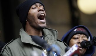 Dontre Hamilton's brother, Nate Hamilton yells on the steps of the federal courthouse Monday, Dec. 22, 2014, in Milwaukee. Milwaukee County District Attorney John Chisholm announced earlier in the day that there would be no charges against former police office Christopher Manney in the fatal shooting of Dontre Hamilton. At right is Maria Hamilton, mother of Dontre Hamilton. (AP Photo/Morry Gash)