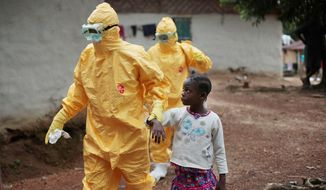 Nine-year-old Nowa Paye is escorted to an ambulance after showing signs of the Ebola infection in the village of Freeman Reserve, located about 30 miles north of Monrovia, Liberia, one of the hardest-hit countries in the current disease epidemic. (associated press)