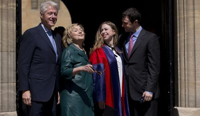 This, May 10, 2014, file photo, shows Former U.S. Secretary of State Hillary Rodham Clinton, second left, as she takes off her sunglasses to pose for a group photograph with her husband former U.S. President Bill Clinton, left, their daughter Chelsea, second right, and her husband Marc Mezvinsky, as they leave after they all attended Chelsea's Oxford University graduation ceremony at the Sheldonian Theatre in Oxford, England. (AP)