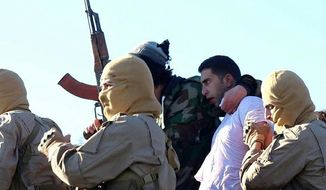 This image posted by the Raqqa Media Center, which monitors events in territory controlled by Islamic State militants with the permission of the extremist group, shows militants with a captured pilot, center right, wearing a white shirt in Raqqa, Syria, Wednesday, Dec. 24, 2014. Islamic State group militants captured a Jordanian pilot, Mu'ath Safi Yousef al-Kaseasbeh, after his warplane went down in Syria, Jordan said Wednesday, the first such capture since the international coalition's air campaign against the group began. The pilot's family confirmed that it is al-Kaseasbeh shown in the image. (AP Photo/Raqqa Media Center)