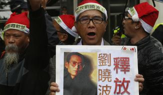 "An anti-Beijing protester holds a placard with picture of jailed Chinese human rights activist Liu Xiaobo during a rally outside the Chinese liaison office in Hong Kong Thursday, Dec. 25, 2014. They demanded to release Chinese human rights activists. The placard reads ""Release Liu Xiaobo."" (AP Photo/Kin Cheung)"