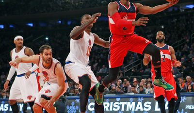 Wizards guard John Wall goes up for a layup after breaking through the defense of New York Knicks guard Jose Calderon (3) and center Samuel Dalembert (11) on Thursday. Wall had 24 points, 11 assists and six rebounds in the Wizards' 102-91 victory.