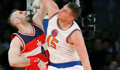 Wizards center Marcin Gortat dunks over New York Knicks center Cole Aldrich in the second half on Thursday. (Associated Press)