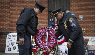FILE - In this Monday, Dec. .22, 2014, file photo, members of the New Rochelle, N.Y. police department place a wreath at a makeshift memorial near the site where NYPD officers Rafael Ramos and Wenjian Liu were murdered in the Brooklyn borough of New York, Monday, Dec. 22, 2014. Police say Ismaaiyl Brinsley ambushed the two officers in their patrol car in broad daylight Saturday, fatally shooting them before killing himself inside a subway station. (AP Photo/John Minchillo, File)
