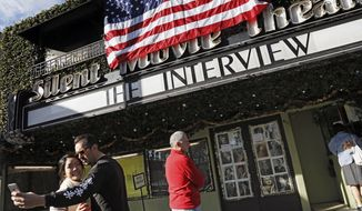 """Bernard Denney takes a selfie with his girlfriend Maho Tanaka, left, in front of the Cinefamily at Silent Movie Theater in Los Angeles on Thursday, Dec. 25, 2014 prior to attending the movie """"The Interview."""" The film's Christmas Day release was canceled by Sony after threats of violence by hackers linked to North Korea, but the release was reinstated in some independent theaters and through a variety of digital platforms. (AP Photo/Richard Vogel)"""