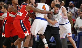 From left, Washington Wizards guard Bradley Beal, Wizards forward Rasual Butler (8), and forward Kris Humphries restrain New York Knicks forward Quincy Acy (4) as an NBA official gets in the middle of an on-court scuffle between Acy and Wizards guard John Wall in the second half of an NBA basketball game at Madison Square Garden in New York, Thursday, Dec. 25, 2014. Acy was ejected from the game and Wall was charged with a technical foul after the incident. New York Knicks guard Pablo Prigioni is at far right in the group. (AP Photo/Kathy Willens)