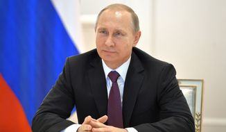 Russian President Vladimir Putin smiles during a live video link with members of Russian Geographical Society expedition to the Southern Pole in Moscow's Kremlin, Russia on Friday, Dec. 26, 2014. (AP Photo/RIA Novosti, Alexei Druzhinin, Presidential Press Service)