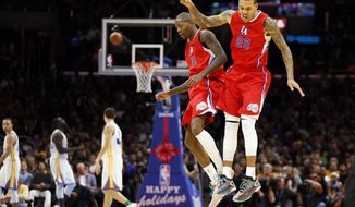 Los Angeles Clippers' Jamal Crawford, second right, celebrates scoring with Matt Barnes, right, against the Golden State Warriors during the second half of an NBA basketball game Thursday, Dec. 25, 2014, in Los Angeles. The Clippers won 100-86. (AP Photo/Danny Moloshok)