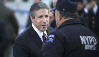 Patrolman's Benevolent Association president Patrick Lynch shakes the hand of an officer outside the wake of officer Rafael Ramos at Christ Tabernacle Church, in the Glendale section of Queens, Friday, Dec. 26, 2014, in New York. Ramos was killed Dec. 20 along with his partner, Officer Wenjian Liu, as they sat in their patrol car on a Brooklyn street. The shooter, Ismaaiyl Brinsley, later killed himself. (AP Photo/John Minchillo)