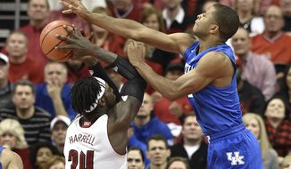 Kentucky's Aaron Harrison, right, attempts to block a shot by Louisville's Montrezl Harrell during the second half of an NCAA college basketball game Saturday Dec. 27, 2014, in Louisville, Ky. Kentucky won 58-50. (AP Photo/Timothy D. Easley)