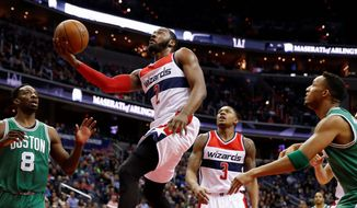 Wizards guard John Wall had many reasons to be happy on Saturday, including a 360-degree layup against the Celtics. The Wizards head out west this week with a 21-8 record. (Associated Press)