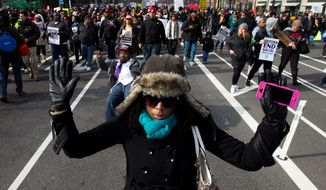 Demonstrators march on Pennsylvania Avenue toward Capitol Hill on Dec. 13. The ongoing protests have cost District police about $3 million. (Associated Press)