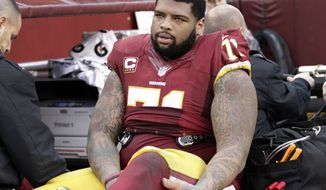 Washington Redskins tackle Trent Williams (71) is taken off the field after an injury during the second half of an NFL football game against the Dallas Cowboys in Landover, Md., Sunday, Dec. 28, 2014. (AP Photo/Mark Tenally)