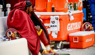 Washington Redskins quarterback Robert Griffin III (10) sits on the bench near the end of the fourth quarter as the Washington Redskins play the Dallas Cowboys the at FedExField, Landover, Md., Sunday, December 28, 2014. (Andrew Harnik/The Washington Times)