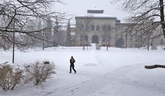 A campus police officer makes the rounds in a snowstorm, making sure doors are locked for holiday vacation on the largely deserted campus of the University of Colorado, in Boulder, Colo., Monday, Dec. 29, 2014. (AP Photo/Brennan Linsley) ** FILE **