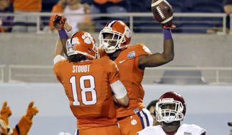 Clemson wide receiver Mike Williams, center, celebrates his 26-yard touchdown with teammate quarterback Cole Stoudt (18) as Oklahoma linebacker Ogbonnia Okoronkwo (82) looks on during the first half of the Russell Athletic Bowl NCAA college football game in Orlando, Fla., Monday, Dec. 29, 2014. (AP Photo/John Raoux)