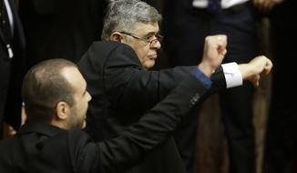 Nikos Michaloliakos, the jailed leader of the extreme right Golden Dawn party, centre, signals against the government, at the parliament in Athens on Monday, Dec. 29, 2014. Parliament failed to elect a new Greek president after three rounds of voting, triggering an early general election on Jan. 25, which could see a pro-bailout coalition lose power. Michaloliakos is awaiting trial on charges of membership of a criminal organization. (AP Photo/Thanassis Stavrakis)