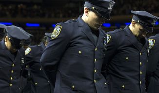 New recruits bow their heads for a moment of silence for deceased officers Rafael Ramos and Wenjian Liu during a New York Police Academy graduation ceremony, Monday Dec. 29, 2014, at Madison Square Garden in New York. Nearly 1000 officers were sworn in as tensions between city hall and the NYPD continued following the Dec. 20 shooting deaths of officers Ramos and Liu. (AP Photo/John Minchillo)
