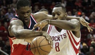Houston Rockets center Joey Dorsey (8) and Washington Wizards forward Kevin Seraphin go after a loose ball during the fourth quarter of an NBA basketball game, Monday, Dec. 29, 2014, in Houston. The Wizards won 104-103. (AP Photo/Patric Schneider)