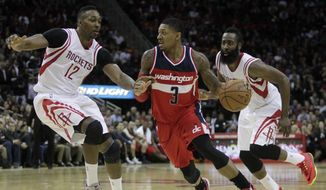 Washington Wizards guard Bradley Beal (3) is defended by Houston Rockets center Dwight Howard (12), and guard James Harden during the fourth quarter of an NBA basketball game, Monday, Dec. 29, 2014, in Houston. (AP Photo/Patric Schneider)