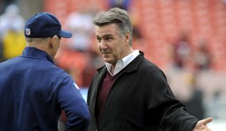 Redskins President and General Manager Bruce Allen, right, talks with Dallas Cowboys defensive coordinator Rod Marinelli prior to the start of their NFL football game in Landover, Md., Sunday, Dec. 28, 2014. The Cowboys defeated the Redskins 44-17.  (AP Photo/Richard Lipski)