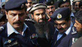 Pakistani police officers escort Zaki-ur-Rahman Lakhvi, center, the main sispect in the Mumbai terror attacks in 2008, after his court appearance in Islamabad, Pakistan, Tuesday, Dec 30, 2014. Pakistani police have rearrested Lakhvi, officials said Tuesday, quashing expectations that he might be soon freed. (AP Photo/Anjum Naveed)