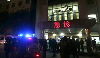 In this photo released by China's Xinhua News Agency, medical workers stand outside the emergency ward of the No. 1 People's Hospital of Shanghai after a stampede caused casualties among people who took part in New Year's celebrations in Shanghai, early on Thursday,  Jan. 1, 2015. The report says the death and injuries occurred at the city's riverfront Bund area, which can be jammed with spectators for major events.  (AP Photo/Xinhua, Ding Ting) NO SALES