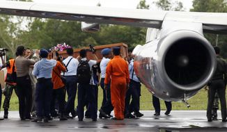 Members of the National Search And Rescue Agency (BASARNAS) carry a coffin containing a body of one of the victims on board the ill-fated AirAsia Flight 8501, to transfer to Surabaya, at the airport in Pangkalan Bun, Indonesia, Wednesday, Dec. 31, 2014. (AP Photo/Achmad Ibrahim)