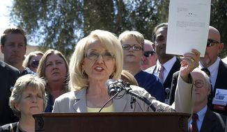 FILE - In a March 12, 2013 file photo, Arizona Gov. Jan Brewer holds a copy of the Medicaid Restoration Plan draft bill at the Capitol in Phoenix. The Arizona Supreme Court on Wednesday, Dec. 31, 2014, allowed a lawsuit challenging Brewer's Medicaid expansion plan to move forward, a decision that deals a major blow to the outgoing governor's signature achievement. The high court agreed that 36 Republican lawmakers can sue Brewer over the legality of a hospital assessment that funds the expansion plan. (AP Photo/Matt York, File)