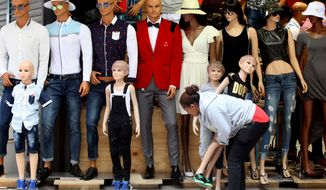 A shopkeeper places a mannequin outside a clothing store in a busy mall in downtown Johannesburg, Wednesday, Dec. 31, 2014 on New Year's Eve. (AP Photo/Denis Farrell)