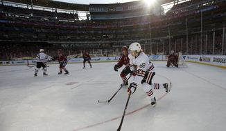Chicago Blackhawks right wing Patrick Kane (88) skates with the puck as he is covered by Washington Capitals defenseman Matt Niskanen (2) in the first period of the Winter Classic outdoor NHL hockey game at Nationals Park, Thursday, Jan. 1, 2015, in Washington. (AP Photo/Alex Brandon)