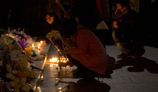 Residents light candles, incense sticks and place flowers at the site of a deadly stampede to commemorate the victims in Shanghai, China, Thursday, Jan. 1, 2015.  New Year's revelers jammed along Shanghai's historic riverfront stampeded about a half hour before midnight Wednesday, killing at least 35 people and injuring 43 others, Chinese media reported, although officials have not yet determined what triggered the stampede. (AP Photo/Ng Han Guan)