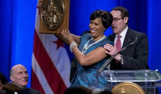 Washington Mayor Muriel Bowser holds the seal of the District of Columbia after accepting it from former Mayor Vincent Gray, right, as council chairman Phil Mendelson watches at left, during the District of Columbia Mayoral Inauguration ceremony at the Convention Center in Washington, Friday, Jan. 2, 2015. (AP Photo/Carolyn Kaster)