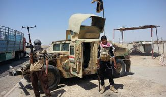 In this file photo taken Thursday, June 19, 2014, Islamic State group militants stand with a captured Iraqi army Humvee at a checkpoint outside Beiji refinery, some 250 kilometers (155 miles) north of Baghdad, Iraq. (AP Photo, File)