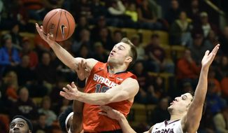Syracuse's Trevor Cooney. center, grabs a rebound against Virginia Tech's  Devin Wilson (11) during the first half of an NCAA college basketball game Saturday, Jan. 3, 2015, in Blacksburg, Va. (AP Photo/Don Petersen)