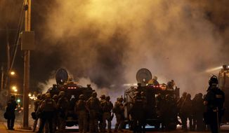 In this Aug. 17, 2014, file photo, police wait to advance after tear gas was used to disperse a crowd during a protest for Michael Brown, who was killed by a police officer in Ferguson, Mo. (AP Photo/Charlie Riedel, File)