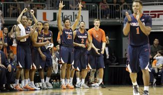 Virginia players celebrate after Justin Anderson (1) scored against Miami in the first half of an NCAA college basketball game in Coral Gables, Fla., Saturday, Jan. 3, 2015. Virginia won 89-80 in double overtime. (AP Photo/Alan Diaz)
