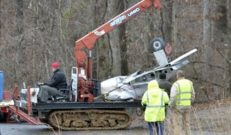 Salvage workers bring out part of a Piper PA-34's fuselage, wing, and landing gear from a crash site Sunday, Jan. 4, 2015, in Kuttawa, Ky. (AP Photo/Timothy D. Easley)