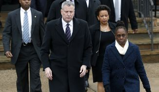 New York City Mayor Bill de Blasio, center, walks with his wife Chirlane McCray, right, following funeral services for New York City police officer Wenjian Liu at Aievoli Funeral Home, Sunday, Jan. 4, 2015, in the Brooklyn borough of New York. Liu and his partner, officer Rafael Ramos, were killed Dec. 20 as they sat in their patrol car on a Brooklyn street. The shooter, Ismaaiyl Brinsley, later killed himself. (AP Photo/Julio Cortez)