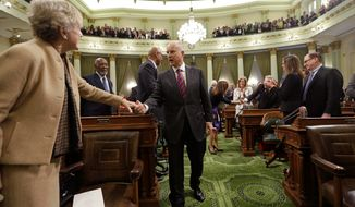 California Gov. Jerry Brown (center) is greeted by lawmakers on the floor of the Assembly Chambers before his inauguration at the state Capitol Monday. He laid out ambitious 2030 goals for combating global warming, led by a 50 percent drop in petroleum use by cars and trucks. (Associated Press)
