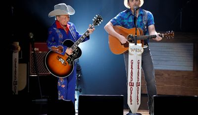 """Country music stars Brad Paisley (right) and Little Jimmy Dickens perform """"Will the Circle be Unbroken?"""" as the opening song as the curtain goes up in the Grand Ole Opry House in September 2010, in Nashville, Tennessee. Mr. Dickens was inducted into the Opry in 1948 by the """"King of Country Music"""" Roy Acuff. (Associated Press photographs)"""
