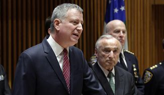"""New York Mayor Bill de Blasio, left, accompanied by New York City Police Commissioner William Bratton, center, addresses a news conference at New York City Police headquarters, Monday, Jan. 5, 2015. De Blasio says it was """"disrespectful"""" that some NYPD officers turned their backs to him during a pair of funerals for slain police officers. (AP Photo/Richard Drew)"""
