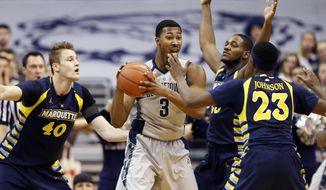 Marquette center Luke Fischer (40), forward Steve Taylor Jr. and guard JaJuan Johnson (23) surround Georgetown forward Mikael Hopkins (3) during the first half of an NCAA college basketball game, Tuesday, Jan. 6, 2015, in Washington. (AP Photo/Alex Brandon)