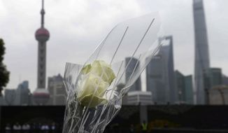 A bouquet of flowers is placed for a New Year's Eve stampede victim at the site of the tragic accident in Shanghai, China, Tuesday, Jan. 6, 2015. (Associated Press) ** FILE **
