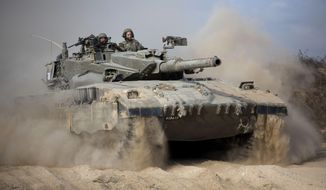 In this Friday, July 18, 2014, file photo, an Israeli tank moves into position near Israel and Gaza border. (AP Photo/Dusan Vranic, File)