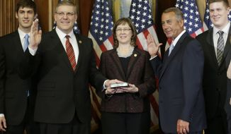House Speaker John Boehner of Ohio, right, administers the House oath to Rep. Barry Loudermilk R-Ga., during a ceremonial re-enactment swearing-in ceremony, Tuesday, Jan. 6, 2015, in the Rayburn Room on Capitol Hill in Washington. (AP Photo/Pablo Martinez Monsivais)