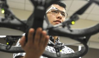 In this Oct. 8, 2014 photo, undergraduate researcher Christopher Rios uses Google Glass to control a drone in mechanical engineering professor Ahmed Mahdy's classroom at Texas A&M Corpus Christi, in Corpus Christi, Texas. (AP Photo/Pat Sullivan)