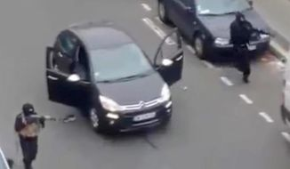 A still from a home video shows gunmen firing their weapons outside the newspaper Charlie Hebdo's Paris office. (Associated Press)