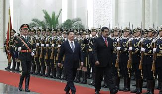Venezuela's President Nicolas Maduro, right, and Chinese President Xi Jinping, center, review an honor guard during a welcome ceremony at the Great Hall of the People in Beijing, China Wednesday, Jan. 7, 2015. (AP Photo/Andy Wong, Pool)
